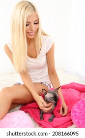 Beautiful young woman with gray sphinx cat sitting on carpet in room