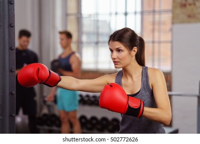 Beautiful young woman in gray tank top and red boxing gloves practicing boxing techniques by herself