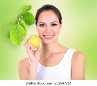 Beautiful young woman with green apple on light green background