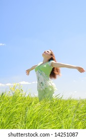 Beautiful young woman in green field at blue sky background