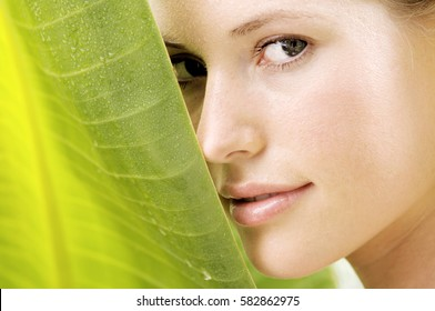 beautiful young woman with green leaf