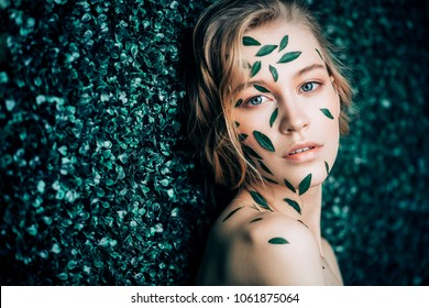 Beautiful young woman with green leaves on her face over green background. Cosmetics and makeup.