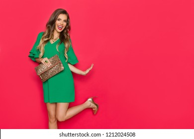 Beautiful young woman in green mini dress and high heels is standing on one leg, holding gold clutch purse, looking at camera and laughing. Three quarter length studio shot on red background.