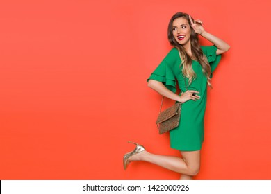 Beautiful young woman in green mini dress, gold clutch bag and high heels is standing on one leg, looking away over the shoulder and smiling. Three quarter length studio shot on orange background.