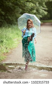 Beautiful young woman in green skirt has fun walking in gumboots on pools after the rain