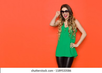Beautiful young woman in green top and sunglasses is looking at camera and laughing. Three quarter length studio shot on orange background.