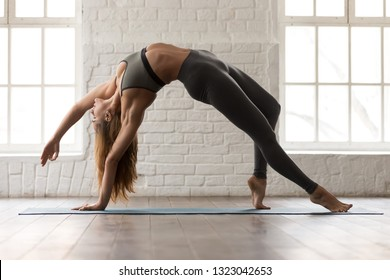 Beautiful young woman in grey sportswear, pants and bra practicing yoga, standing in Wild Thing pose, attractive girl doing Camatkarasana exercise, working out at home or in modern yoga studio