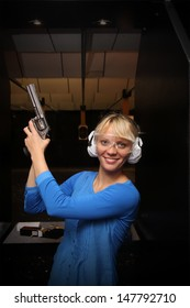Beautiful young woman with the gun on an indoor shooting range