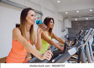 Beautiful young woman at gym doing cardio biking workout