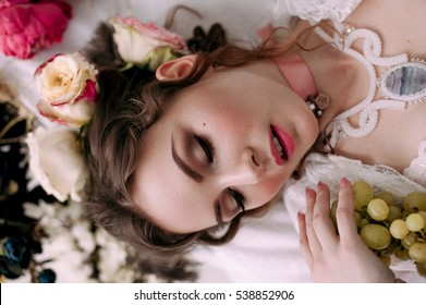 Beautiful young woman, hair decorated with flowers. Perfect makeup. Beauty fashion. Eyelashes. Studio retouched shot. Tender and sweet atmosphere, pastel colors