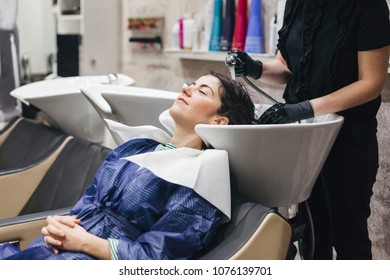 Beautiful young woman to hairdresser while washing head in hair salon