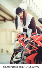 Beautiful young woman, hairstyle and bows outdoors with a motorcycle. Happy and healthy dressed in a Soviet school uniform. girl biker. Concept of fun.