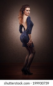 beautiful young woman with hairstyle and bright makeup posing in blue dress