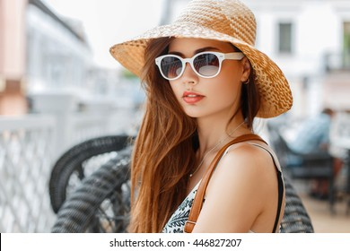 Beautiful young woman with hairstyle and red lips, wearing a hat and sunglasses on a sunny day. The concept of a summer holiday.