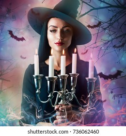Beautiful young woman as halloween witch-magical portrait. Halloween witch casts a spell. Fabulous, spooky voodoo shack. Candles. Fashionable toning. Creative color