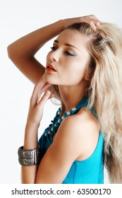 beautiful young woman with hand in long hair wearing bright blue eyeliner and a matching dress with pearls.