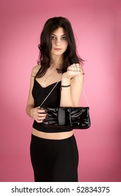 Beautiful young woman with handbag over pink background