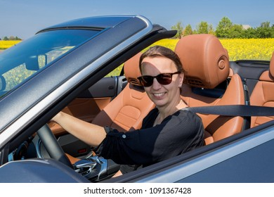 Beautiful young woman happy to drive her convertible car on a country road in summer. she looks at camera.