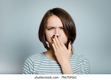 beautiful young woman has nausea, isolated on background, studio photo