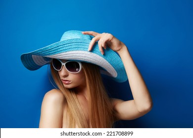 Beautiful Young woman in hat on blue background