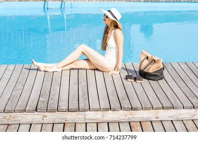 Beautiful young woman in hat relaxing near the swimming pool sitting with bag and slippers on the wooden poolside