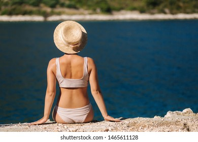 Beautiful young woman in hat sit on the cliff by the beautiful lagoon. Back view of sexy woman sitting by the sea. Background of blue water