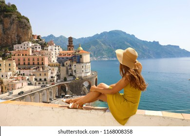 Beautiful young woman with hat sitting on wall looking at stunning panoramic village of Atrani on Amalfi Coast, Italy