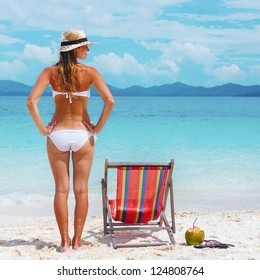 Beautiful Young woman in hat sunbathing on tropical beach