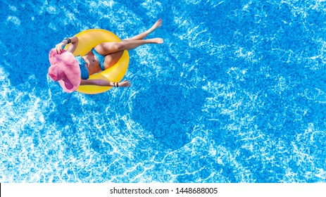Beautiful young woman in hat in swimming pool aerial top view from above, girl in bikini relaxes and swims on inflatable ring donut and has fun in water on family vacation, tropical holiday resort