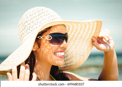 Beautiful young woman in a hat and swimsuit over seaside backgro