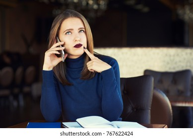 Beautiful young woman have nice conversation on cell telephone. Young  businesswoman sitting in cafe at wooden table and talking on smart phone