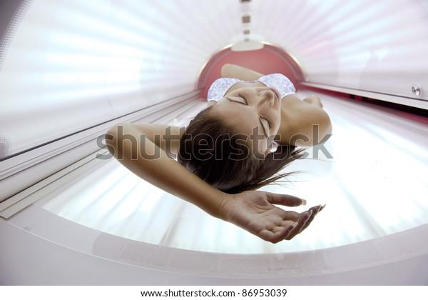Schöne junge Frau hat eine Sonnenbräunungsbehandlung im modernen Solarium