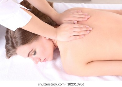 Beautiful young woman having back massage in spa salon