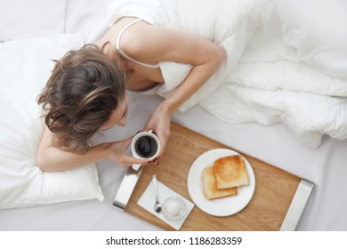 Beautiful young woman having breakfast in bed