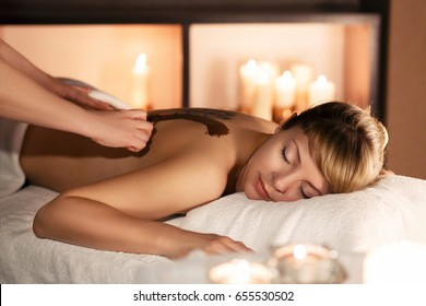 Beautiful young woman having chocolate facial mask apply by beautician and spa massage with candle background