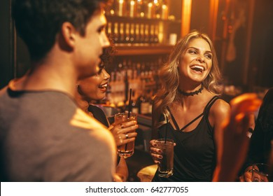 Beautiful young woman having drink at nightclub with friends. Group of people enjoying party in pub.