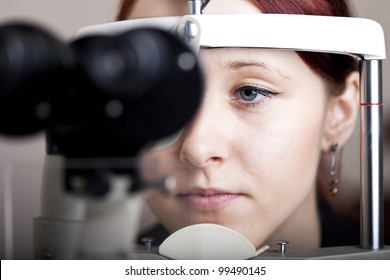 Beautiful young woman having eye test. At the optometrist concept.