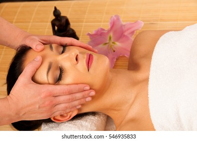 Beautiful young woman having a face massage in wellness studio - spa