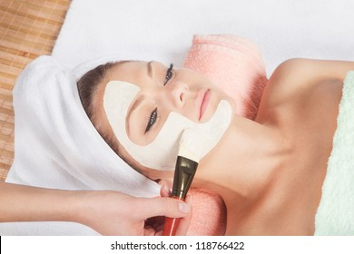 Beautiful young woman having a facial cosmetic mask at spa salon. Girl is having cosmetic treatment.