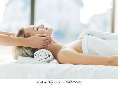 beautiful young woman having facial massage at salon