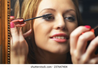 Beautiful young woman having fun while putting make up in front of the old mirror.