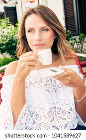 Beautiful young woman having her morning coffee in small café in Italy