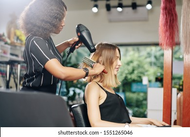 Beautiful young woman having her hair blowdried in beauty salon when getting reay for important event
