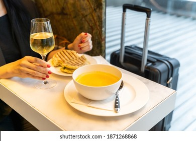 Beautiful young woman having a lunch of yellow vegetarian soup, sandwich and a glass of wine near small black modern luggage near window in departure launch restaurant of an airport. Food and travel.