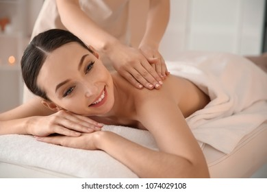 Beautiful young woman having massage with body scrub in spa salon