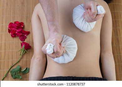 Beautiful young woman having massage with herbal compress balls in spa salon