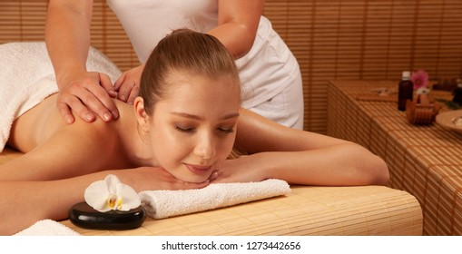 Beautiful young woman having a massage treatment in spa salon - wellness .