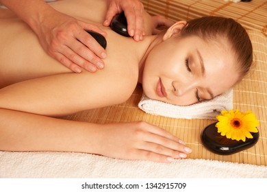 Beautiful young woman having a massage treatment in spa salon - wellness .