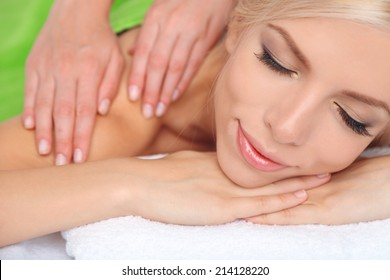 Beautiful young woman having massage in spa salon