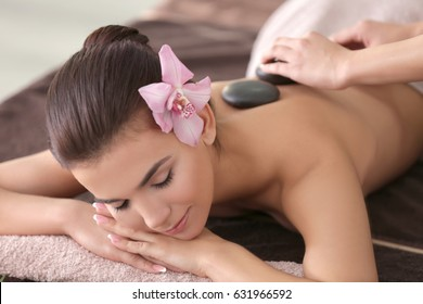 Beautiful young woman having massage with stones in spa salon